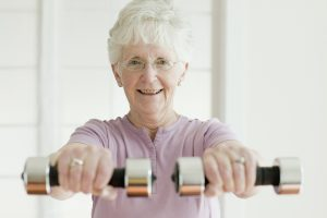 Senior woman lifting weights to help move.